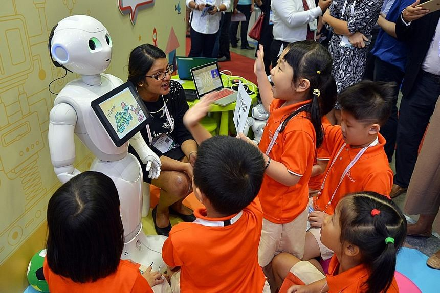 Children interacting with Pepper, one of the two humanoid robots on trial, at the Infocomm Media Business Exchange at Marina Bay Sands yesterday.