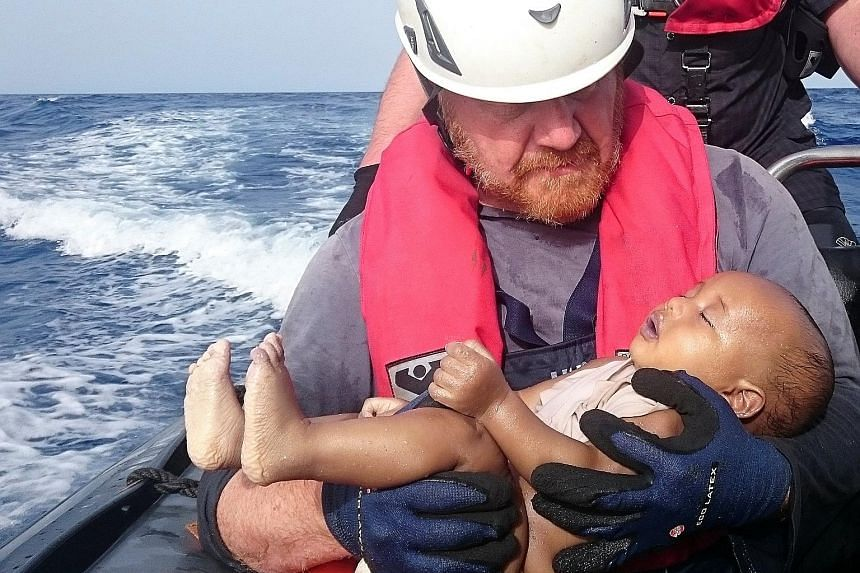 The body of a baby in the arms of a rescuer from Sea-Watch, which is a German non-governmental organisation. The body was retrieved from the sea after a wooden boat capsized last Friday off the Libyan coast.
