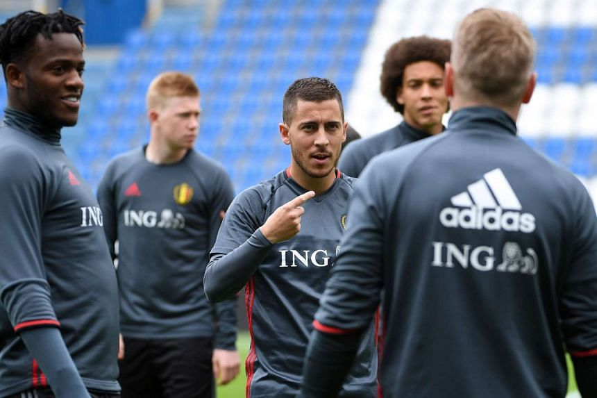 Belgium's team captain Eden Hazard (centre) speaks with teammates during a training session on May 31, 2016.