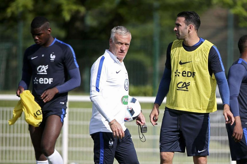 France's national soccer team coach Didier Deschamps (centre) passes by players Paul Pogba (left) and Adil Rami.
