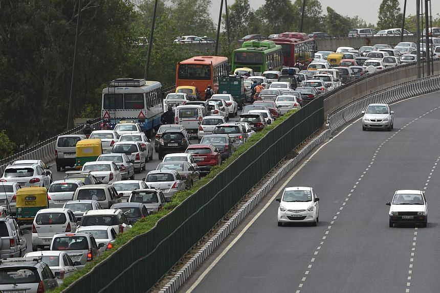 Indian commuters travel on a highway linking Gurgaon to New Delhi.