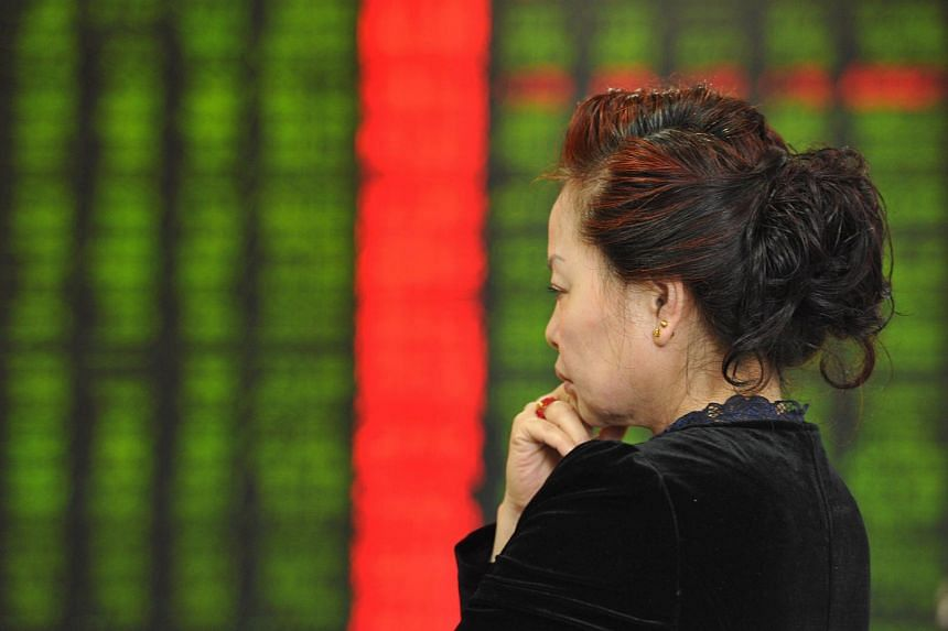 An investor stands in front of a screen showing stock market movements at a securities firm in Fuyang, China.