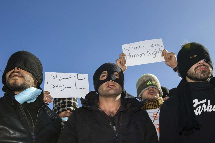 Iranian migrants with their lips symbolically sewn shut protest the dismantlement of their camp in Calais, France, March 4, 2016.