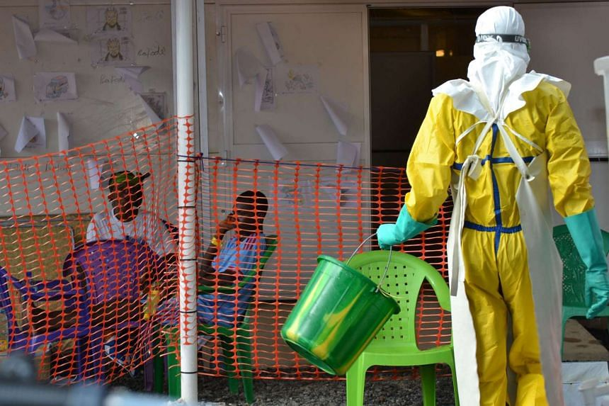 A health worker walking towards patients under quarantine at the Nongo ebola treatment centre in Conakry, Guinea, on Aug 21, 2015.