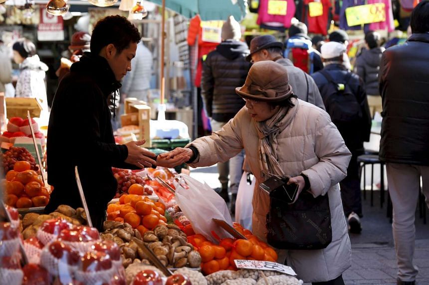 A woman buys fruits outside a vegetable store at Ameyoko shopping district in Tokyo, Japan, on Jan 27, 2016.