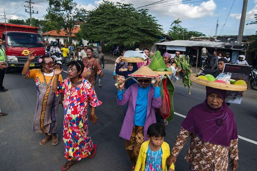 Survivors dressed as women, to show their support for the women who lost their livelihoods, take part in a parade to mark the 10th anniversary of the mudflow disaster in the Sidoarjo district of Java island, on May 29, 2016.