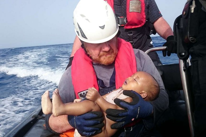 A German rescuer from the humanitarian organisation Sea-Watch holds a drowned migrant baby, off the Libyan coast on May 27, 2016.