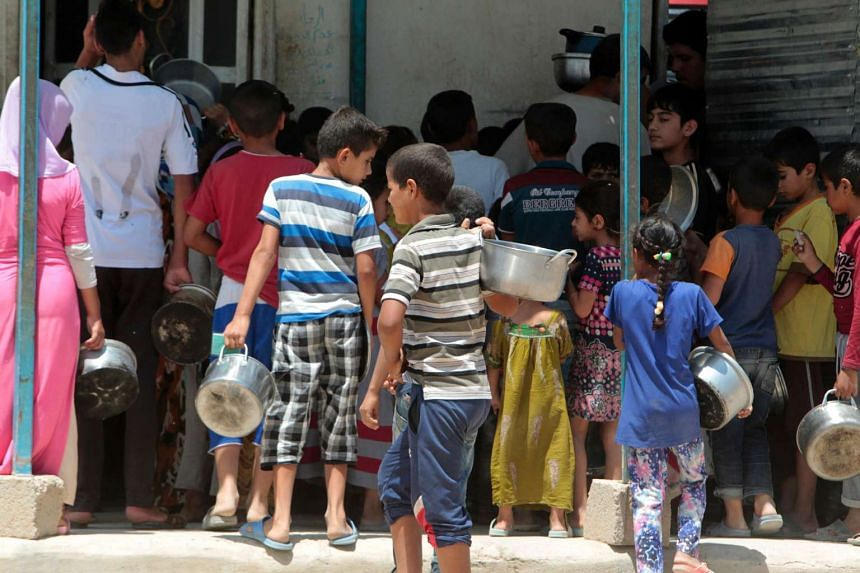 Displaced Iraqis line up to collect donated food at the Alexanzan camp in the Dora neighbourhood in the outskirts of Baghdad, on May 31, 2106.