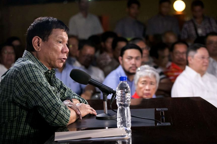 Philippine president-elect Rodrigo Duterte speaks as cabinet members look on during a press conference in Davao, on May 31, 2016.