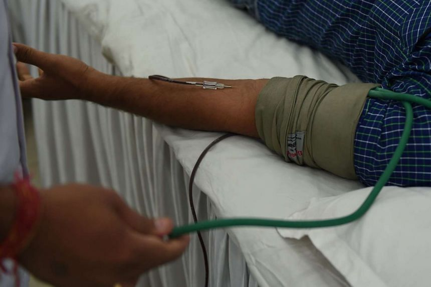 An Indian volunteer donates blood during a blood donation camp in New Delhi, on Sept 24, 2015.