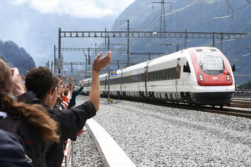 Guests waves at a train that has crossed the tunnel during the opening ceremony of the NEAT Gotthard Base Tunnel near the town of Erstfeld, Switzerland on June 1, 2016.
