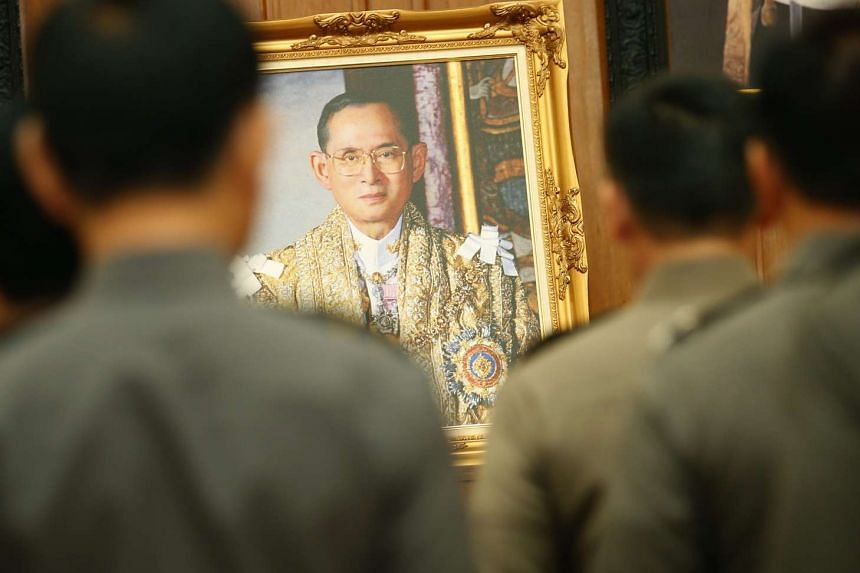 Thai well-wishers pray for the health of King Bhumibol Adulyadej next a picture of the King (centre) in a file photo.
