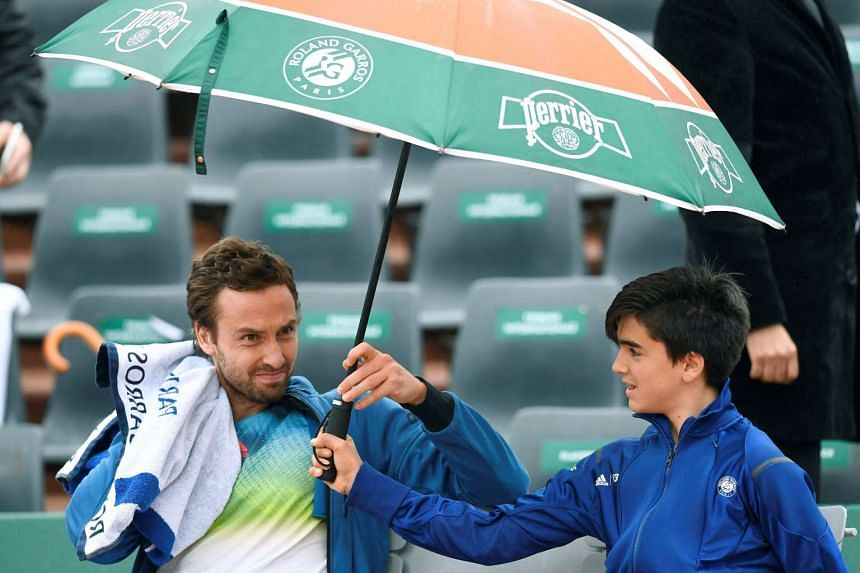Latvia's Ernests Gulbis sits under an umbrella as play is interrupted due to rain at the French Open on May 31, 2016.