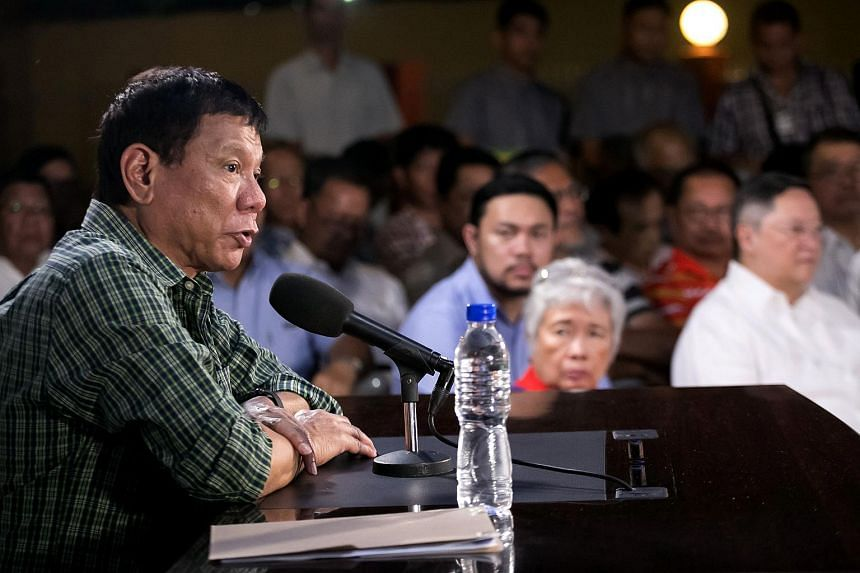 Philippines' president-elect Rodrigo Duterte speaks as cabinet members look on during a press conference in Davao.