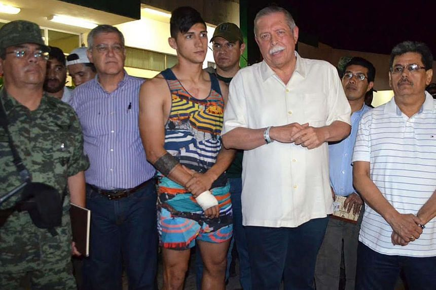 Mexican footballer Alan Pulido with Tamaulipas state Governor Egidio Torre Cantu (right), after receiving treatment for his cut wrist which he suffered while escaping. One of his captors was caught.