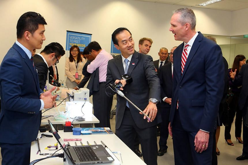 Dr. Koh Pon Koon (centre), Minister of State, Ministry of Trade and Industry, trying the iDriveTM Ultra Powered Stapling System, as Medtronic's President of Asia Pacific Bob White (right) looks on.
