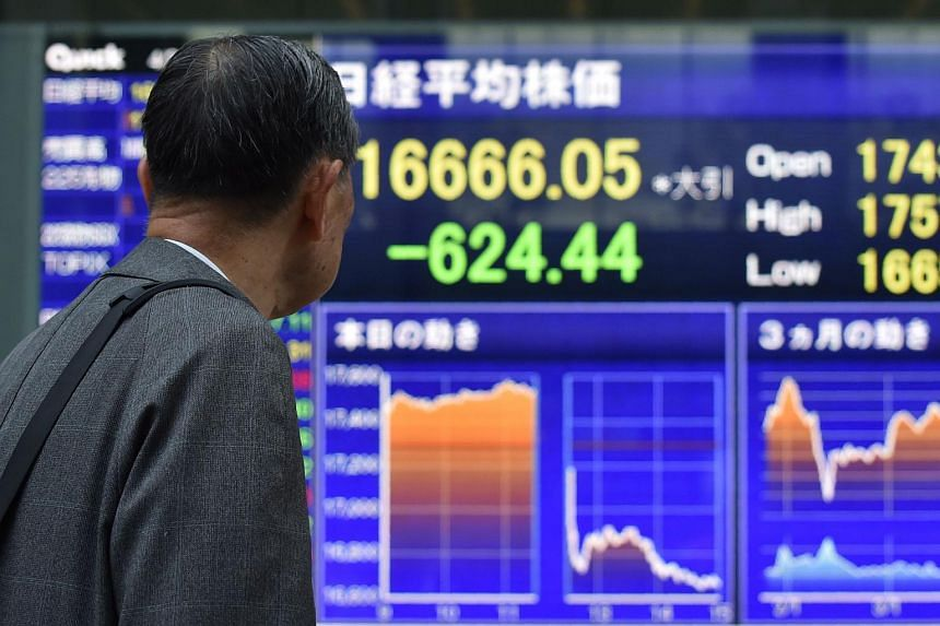 A pedestrian looks at a quotation board flashing the Nikkei key index from the Tokyo Stock Exchange in Tokyo.