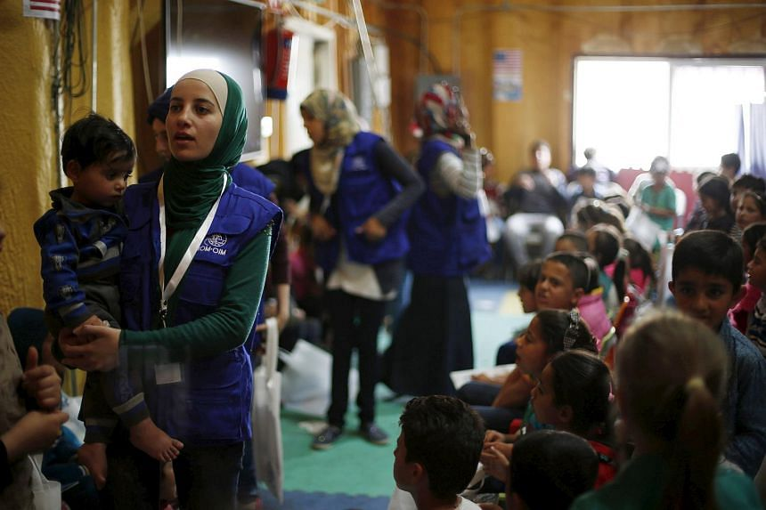 Syrian refugee children play as they wait with their families to register their information at the US processing centre for Syrian refugees.