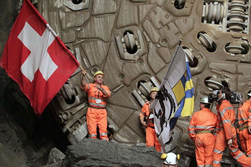 Miners celebrate after breaking through the last section of the Gotthard Base Tunnel.
