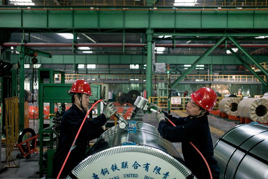 Chinese workers pack steel rolls in a steel factory in Tangshan.