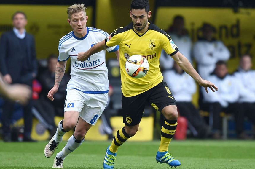 Dortmund's midfielder Ilkay Guendogan (centre) vies for the ball with Hamburg's midfielder Lewis Holtby during the German Bundesliga match, on April 17, 2016.