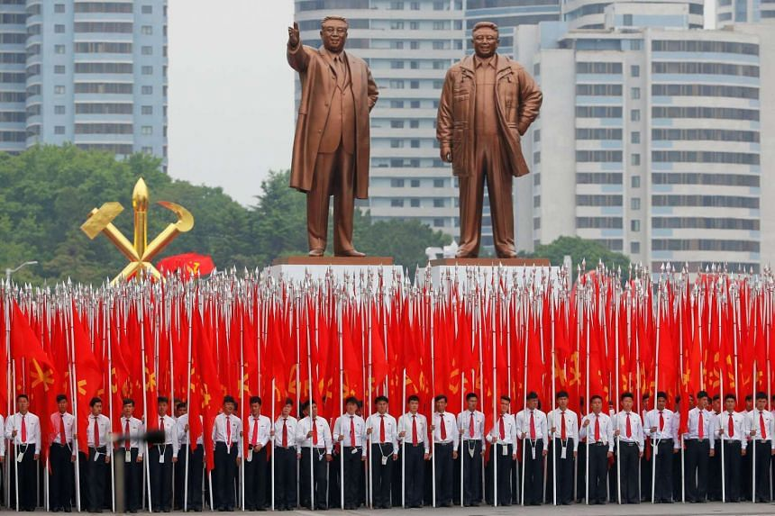 Students carrying party flags stand under statues of former North Korean leaders Kim Il Sung and Kim Jong Il in the main ceremonial square in Pyongyang, North Korea, on May 10, 2016.