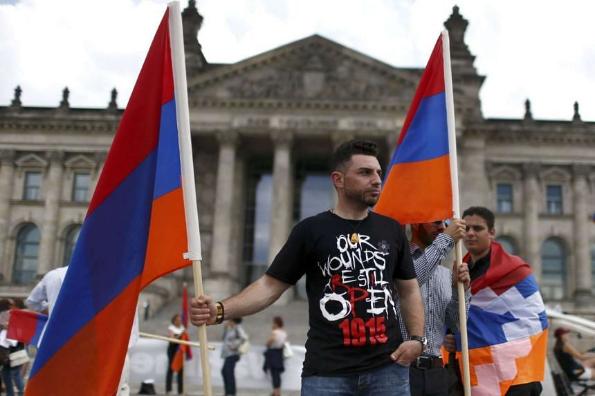Supporters hold Armenian flags in front of the Reichstag, the seat of the lower house of parliament Bundestag in Berlin, Germany, on June 2, 2016.