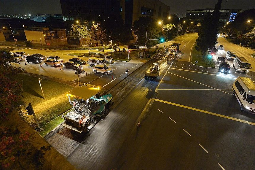 Workers resurfacing the affected section of Jalan Boon Lay last night. It was scheduled to be completed by 2am.