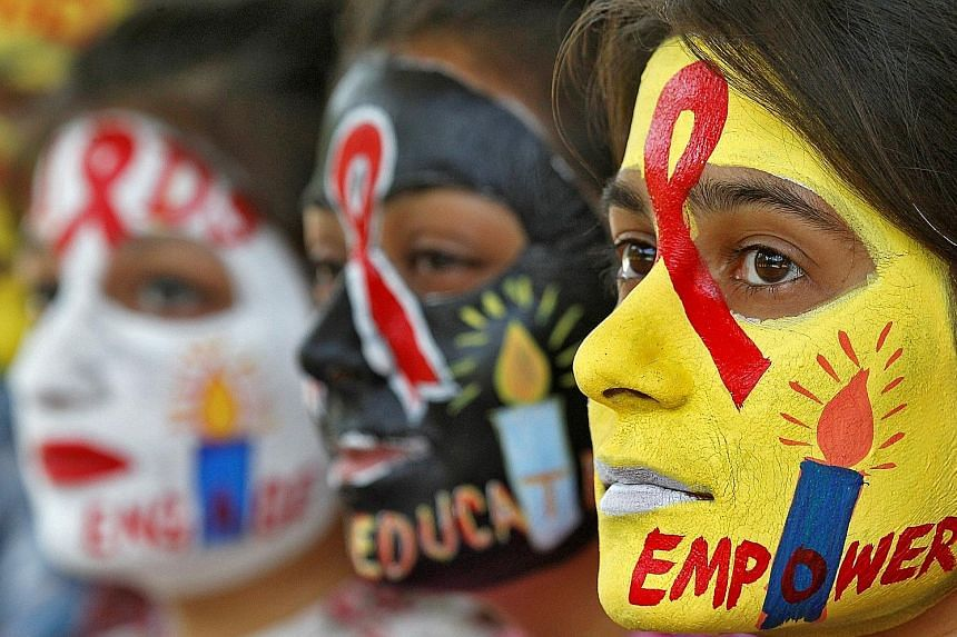 Students with faces painted with HIV/Aids awareness messages at the International Aids Candlelight Memorial, in Chandigarh, India, last month.