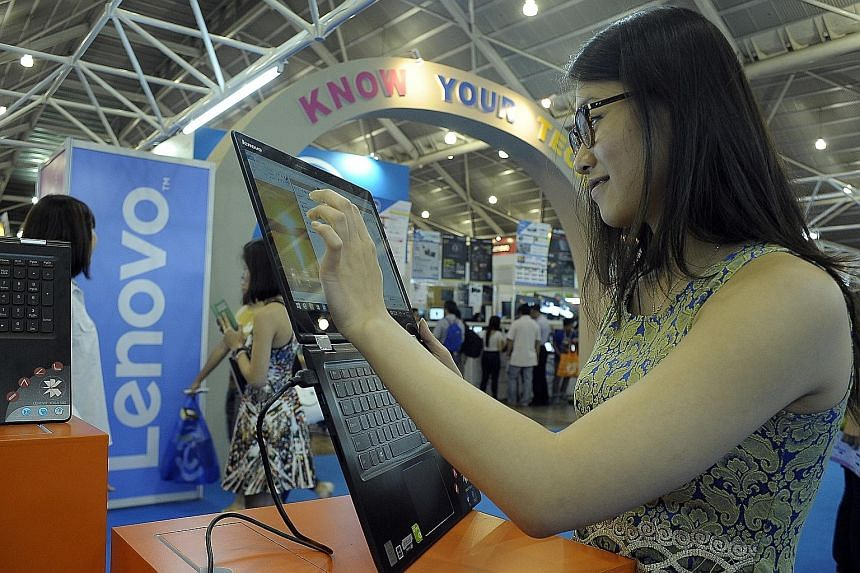 A tech enthusiast looking for bargains at last year's PC Show (left). This year, every $100 spent at the show entitles you to a lucky draw ticket. The top prize is a brand-new Hyundai Elantra Elite sedan car worth $61,000 (without COE).