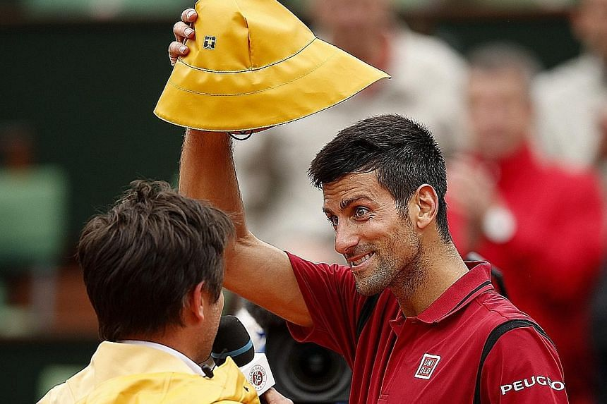 Novak Djokovic of Serbia borrows a rain hat from his interviewer, the former player Fabrice Santoro, after taking three days of play to defeat Roberto Bautista Agut of Spain in the round of 16 at the French Open. Turbulent weather in Paris has create