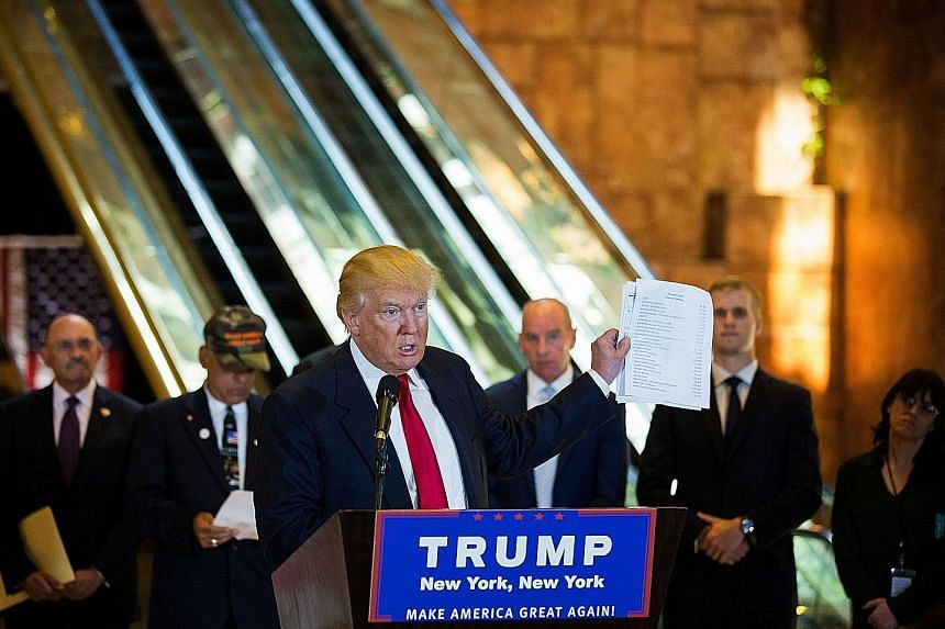Mr Trump holds up a list of charities he said he donated to, after a news outlet reported he had not yet donated the money he promised to military veterans.
