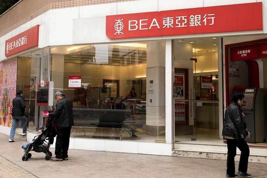 Pedestrians walk past a Bank of East Asia branch in Hong Kong on February 15.