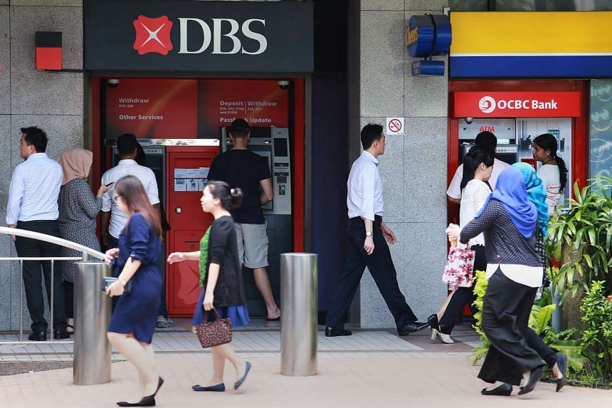 Office workers at DBS and OCBC ATMs at Raffles Place.
