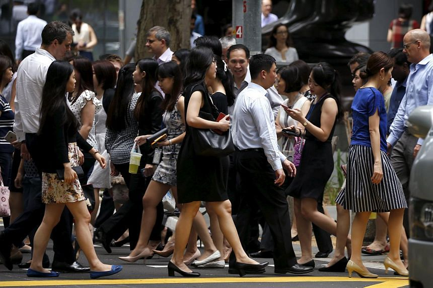 Office workers cross a street during lunch hour at the central business district in Singapore on April 27.
