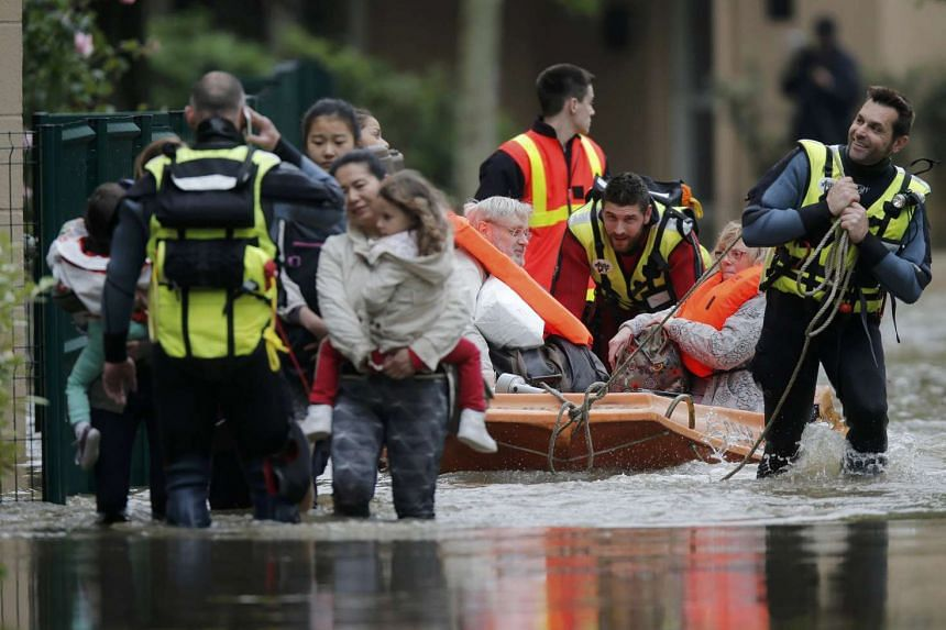 French firefighters evacuating residents from a flooded area after heavy rain in Longjumeau, southern Paris, on June 2, 2016.