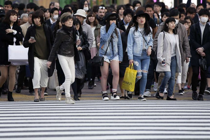 Pedestrians cross an intersection in the Shibuya district of Tokyo, Japan.