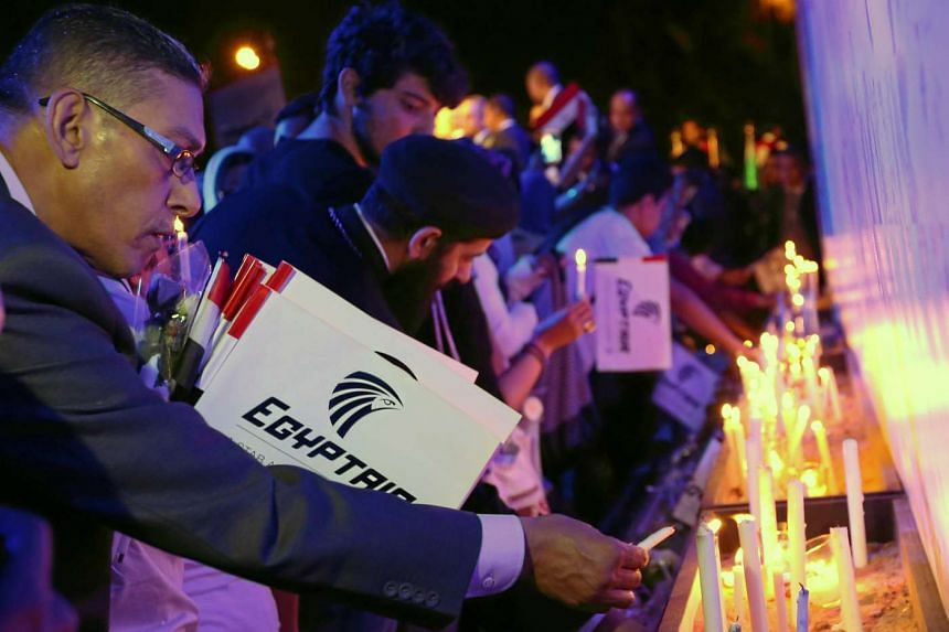 People light candles during a candlelight vigil for the victims of EgyptAir flight 804, at the Cairo Opera House in Cairo, Egypt on May 26, 2016.