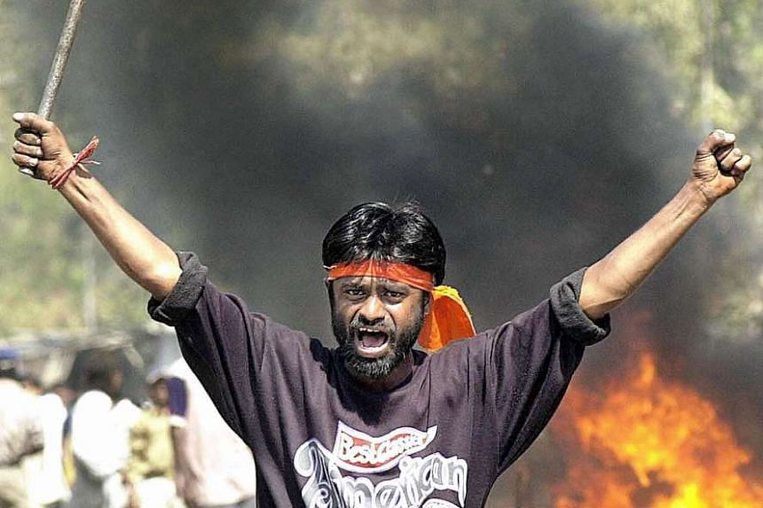 An Indian Bajranj Dal activist armed with a iron stick shouts slogans on a street at Sahapur in Ahmedabad, on Feb 28, 2002.