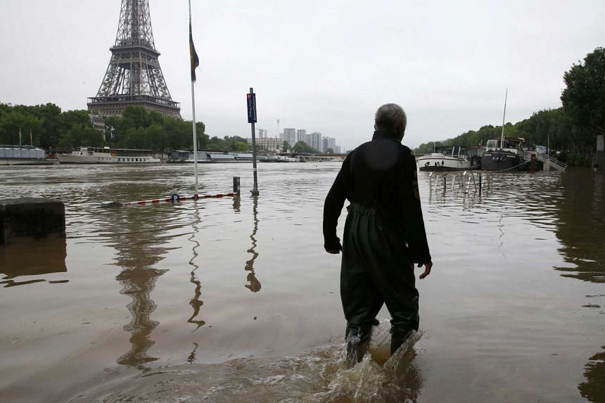 A man walking on a flooded street near the Eiffel towel during flooding on the banks of the Seine River in Paris on June 2, 2016.