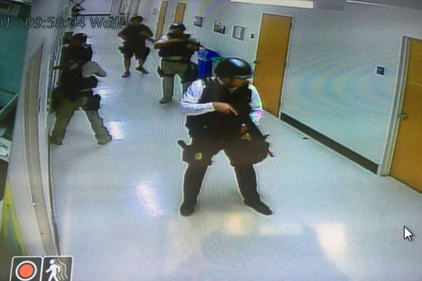 Police officers search corridors and rooms after the report of an active shooter.