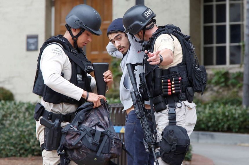 Police officers search a student's belongings at the University of California, Los Angeles (UCLA) campus during lockdown.