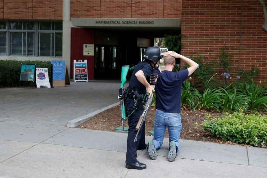 A police officer searches a student at the UCLA campus after it was placed on lockdown.