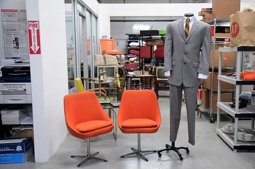 A Lane Price suit and a pair of Don Draer chairs are displayed among items from the American drama series Mad Men at ScreenBid.