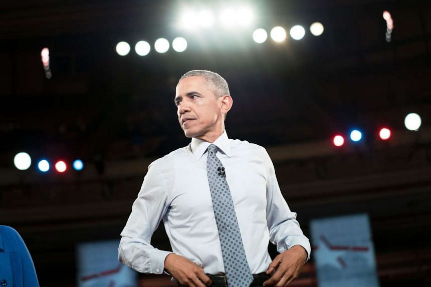 US President Barack Obama waits during a break in filming a town hall meeting for PBS Newshour at the Lerner Theatre.
