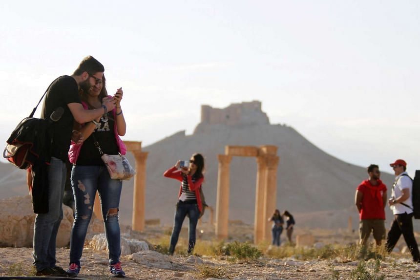 People visit the ruins of post-ISIS Palmyra ahead of a concert in its amphitheatre on May 6, 2016.