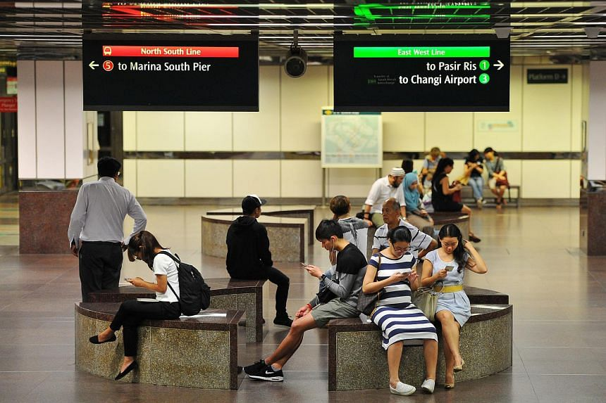 People using mobile phones at City Hall MRT station on June 1.