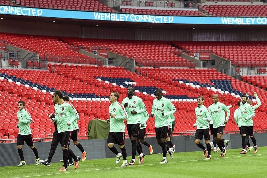 Portuguese national soccer team players warm up during their team's training session at Wembley stadium in London, Britain, on June 1.