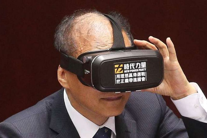Taiwanese Premier Lin Chuan wearing a pair of virtual reality goggles while debating with opposition legislator Huang Kuo-chang in parliament on June 3, 2016.