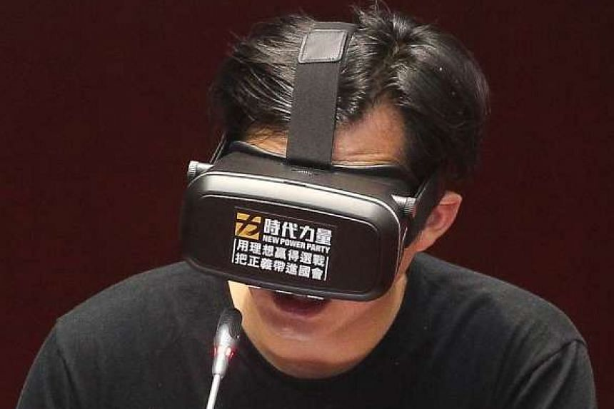 Opposition legislator Huang Kuo-chang debating with Premier Lin Chuan in Taiwan's parliament while wearing a pair of virtual reality goggles, on June 3, 2016.